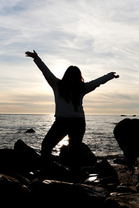 Silhouette of a young woman posing on the beach with her arms up in the air.
