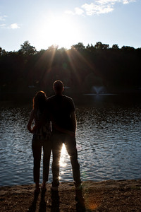 Silhouette of an affectionate couple embracing each other in the early evening hours with back lit lighting.