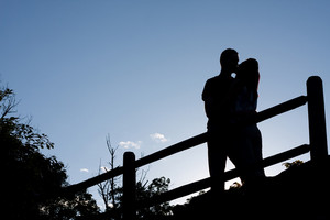 Silhouette of an affectionate couple romantically kissing each other in the early evening hours.