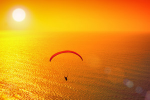 Silhouette of paraglider soaring at sunset