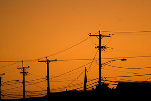 Silhouettes of the power lines and wires in a residential neighborhood backlit by the evening sky.