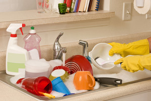 Sink Full of Dishes Being Washed By Hand
