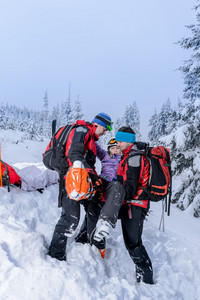 Ski patrol carry injured woman skier on rescue stretcher