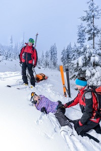Ski patrol helping woman with broken leg lying in snow