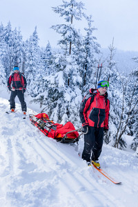 Ski patrol members carry injured skier downhill rescue stretcher