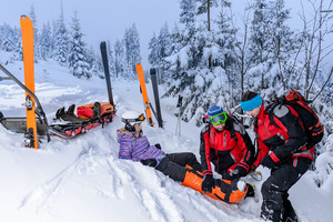 Ski patrol team rescue woman skier with broken leg