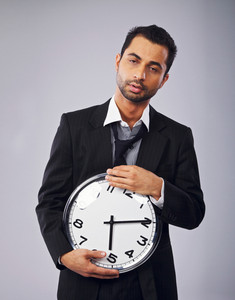 Sleepy office worker holding a clock