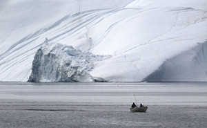 Small boat traveling past a large iceberg