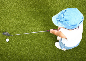 Small Child Playing Golf On A Putting Green