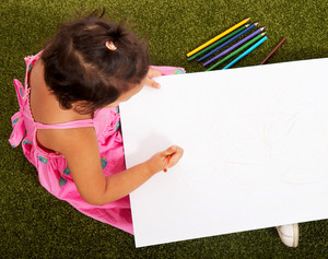 Small Girl Concentrating On Drawing A Picture