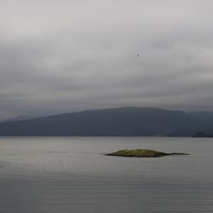 Small, grassy island under a foggy sky