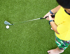 Small Kid Learning To Play Golf