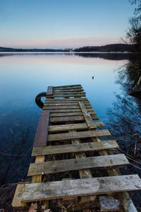 Small pier on lake long exposure photo. Mazury lake district.