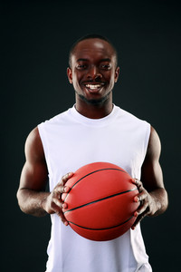 Smiling african american basketball player over black background