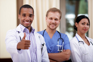 Smiling african-american doctor making thumbs up sign with colleagues standing behind