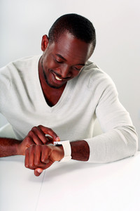 Smiling african man sitting at the table and looking on wristwatch