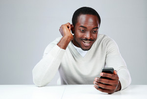 Smiling african man sitting at the table and using smartphone