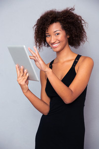 Smiling african woman using tablet computer