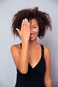 Smiling afro american woman covering her eye