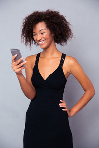 Smiling afro american woman using smartphone