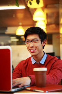 Smiling asian man in glasses working on laptop in office