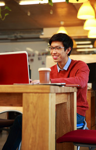 Smiling asian man in glasses working on laptop