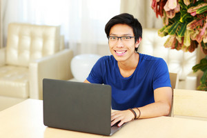 Smiling asian man sitting at the table with laptop