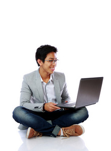 SMiling asian man sitting on the floor and using laptop over white background
