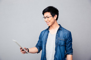 Smiling asian man standing with tablet computer