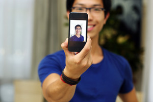Smiling asian man taking self picture with smartphone camera. Focus on smartphone