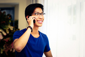 Smiling Asian man talking on the phone at home