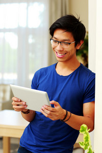 Smiling asian man using tablet computer at home