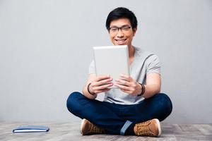 Smiling asian man using tablet computer