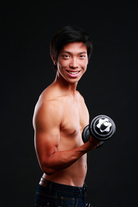 Smiling asian man working out with dumbbell on black backgroung