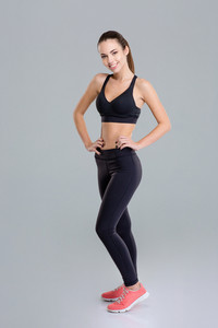 Smiling attractive fitness woman standing and posing over white background