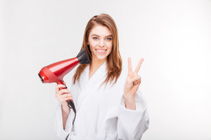 Smiling attractive young woman in bathrobe standing with hair dryer and showing victory sign