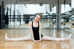 Smiling ballerina doing splits in ballet class