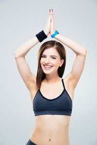 Smiling beautiful sporty woman making yoga exercises over gray background and looking at camera