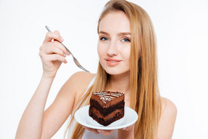 Smiling beautiful young woman eating chocolate cake over white background