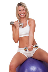 Smiling blond woman exercising with weights on white background