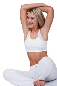 Smiling blond woman stretching on white background