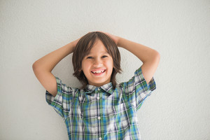 Smiling boy posing in front of a wall with his hands behind his head