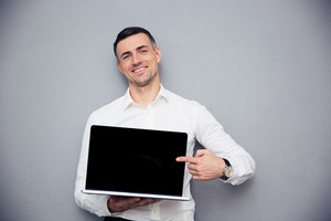 Smiling businessman pointing finger on blank laptop screen over gray background. Looking at camera