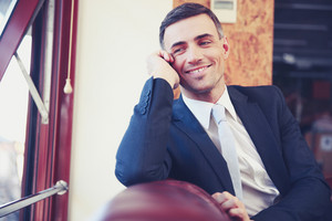 Smiling businessman sitting and looking in window at office