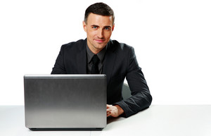 Smiling businessman sitting at the table with laptop isolated on a white background