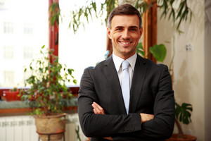Smiling businessman standing with arms folded at office