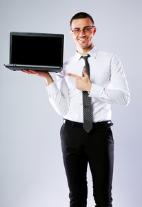 Smiling businessman standing with laptop and showing on it over gray background