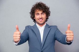 Smiling businessman standing with thumbs up