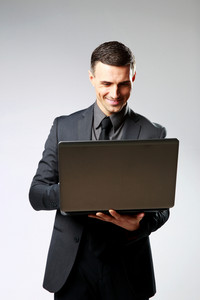 Smiling businessman using laptop on gray background