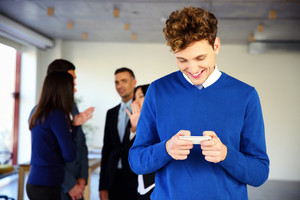 Smiling businessman using smartphone in front of a colleagues